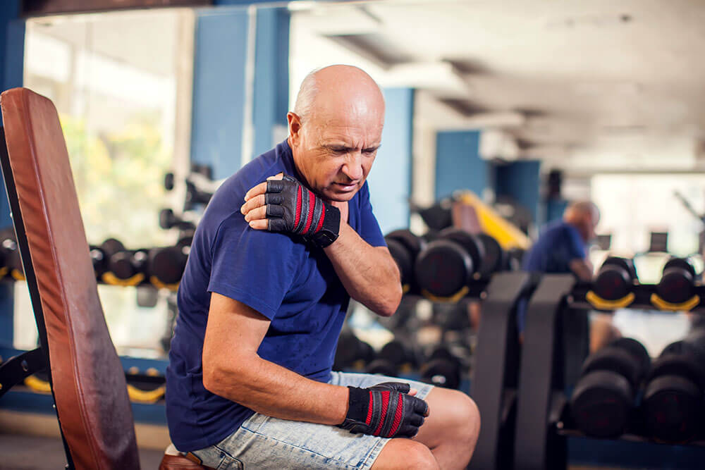 Photo of older man in gym with shoulder pain